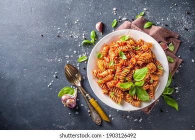 Fusilli pasta with tomato sauce and basil. Traditional italian Fusilli pasta marinara, on dark background copy space