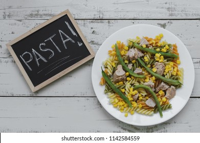"Fusilli pasta with tuna, green beans and sweet corn served on gray wooden table and framed blackboard with text ""Pasta"". top view"
