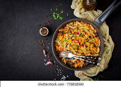Fusilli vegetable paste with pumpkin, Brussels sprouts, paprika and liver pieces on a dark background. View from above