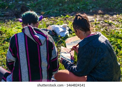 Fusion of cultural & modern music event. Two young people are seen from behind, sitting outdoors in nature and painting pictures on small boards during a native music festival