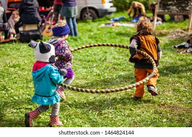 Fusion of cultural & modern music event. Three children are seen carrying a hula hoop through a campsite at a music festival, one boy wears a Native American coat, friends playing in nature
