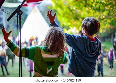 Fusion of cultural & modern music event. Two children are seen dancing on stage during a music festival, raising arms in air, blurry audience and tipi tents are viewed in the background.
