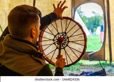 Fusion of cultural & modern music event. An over the shoulder view of a spiritual man playing native drum as he sits inside a teepee tent during a celebration of Native American culture, room for copy