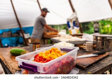 Fusion of cultural & modern music event. A closeup view of chopped vegetables in a plastic container, on a rustic wooden bench inside a tipi tent at a music festival campsite, outdoor food preparation