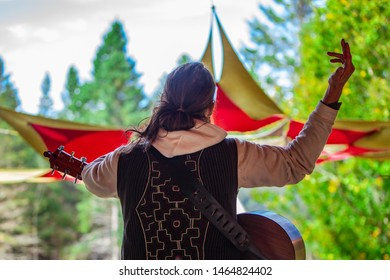 Fusion of cultural & modern music event. A guitar player with long hair in a ponytail is viewed from the rear as he raises his right hand in the air and entertains people at an eclectic music festival
