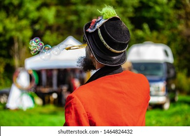 Fusion of cultural & modern music event. A shaman is viewed from the back, in traditional costume, blowing soap bubbles in a campsite at a music festival, blurry RV and tent is seen in background