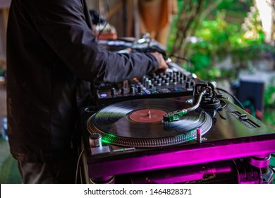 Fusion of cultural & modern music event. A music DJ is viewed closeup, operating an old-fashioned vinyl turntable during an eclectic music festival outdoors, using hands to control knobs.