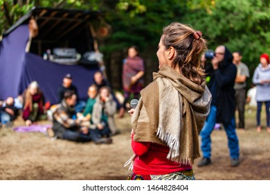 Fusion of cultural & modern music event. A spiritual speaker is viewed from behind and off to the side, as she uses microphone among a crowd of people during a cultural music festival, with copy space