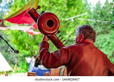 Fusion of cultural & modern music event. An older man is viewed from behind, wearing a brown leather jacket and playing a large traditional native instrument during a music festival outdoors