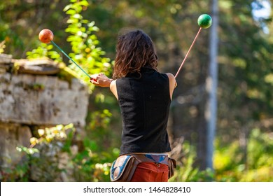 Fusion of cultural & modern music event. An entertainer is viewed from behind, swinging balls against a blurred woodland backdrop, during a cultural music festival in natural environment.