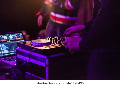 Fusion of cultural & modern music event. A closeup view on the hands of a DJ as he uses an electronic turntable attached to a laptop during a music festival, viewed from behind by night.