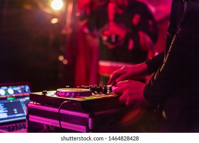 Fusion of cultural & modern music event. A close up view on modern electronic music equipment, operated by a disc jockey during a music festival by night, with copy space to the left.