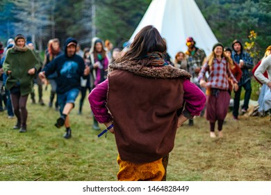 Fusion of cultural & modern music event. A bohemian dance tutor is viewed from behind, as blurry people are seen following her moves in the background, during a native music festival in nature