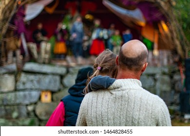Fusion of cultural & modern music event. A dad with a bald spot on his head is seen from the back, lifting his daughter up to watch musicians perform on stage at a music gig in nature.