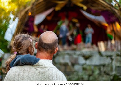 Fusion of cultural & modern music event. A bald headed father is viewed from behind, holding his his little girl as they watch a live band perform at a family music festival, with copy space.