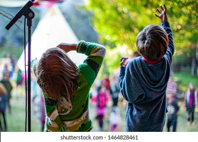 Fusion of cultural & modern music event. Children are seen from behind, standing on stage next to a mic stand during a family friendly music festival combing different cultures.