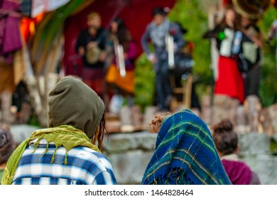 Fusion of cultural & modern music event. Hippies are viewed from behind, watching a blurry band perform folk music in the background, traditional instruments are played during cultural gig in nature.