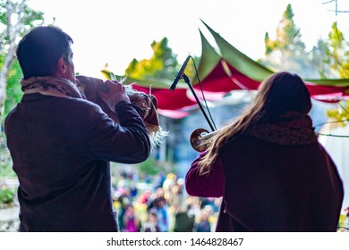 Fusion of cultural & modern music event. Traditional musicians are viewed from behind, playing trombones on stage during a music festival, blurry audience is seen in the background, with white sky