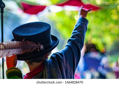 Fusion of cultural & modern music event. A child is viewed from the back, wearing traditional beaver hat with feather raising his arm in the air to give the sign of the horns gesture at music festival