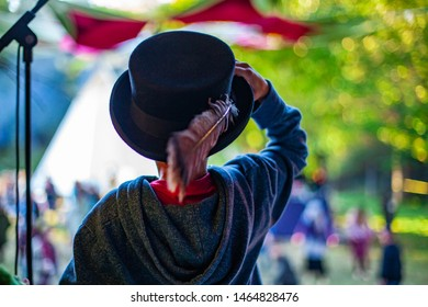 Fusion of cultural & modern music event. A young boy is viewed from behind, wearing an old-fashioned top hat with sacred feather, at a music gathering that mixes modern beats with native cultures.