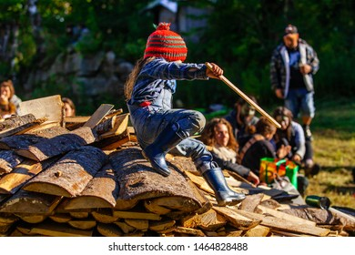 Fusion of cultural & modern music event. A side view of a young girl climbing on a pile of chopped logs and holding a stick during a music festival, blurry people are seen in the background