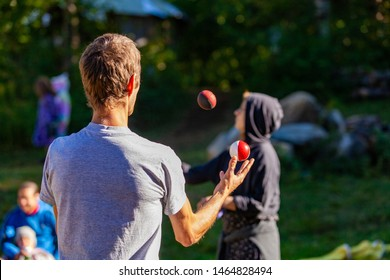 Fusion of cultural & modern music event. A slim Caucasian man is viewed from behind, juggling balls at a music festival, blurry millennials are seen in the background, copy space to the right