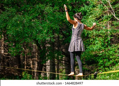Fusion of cultural & modern music event. A young Caucasian girl is seen barefooted, walking a tightrope in the woods as young people gather to celebrate different lifestyles, with copy space.