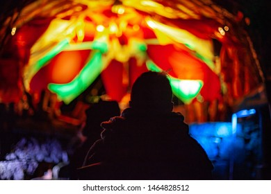 Fusion of cultural & modern music event. A backlit view of people at music festival celebrating native culture and modern sounds colorful lights are blurry in the background by night over a man's head