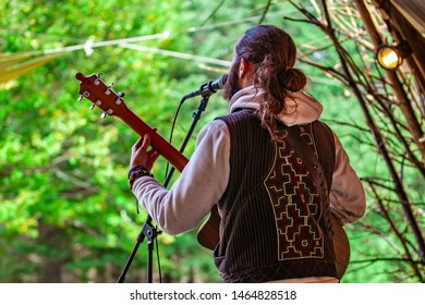 Fusion of cultural & modern music event. A young bearded guy with long hair in ponytail is viewed singing and playing an instrument outdoors during a cultural music festival blurry trees in background