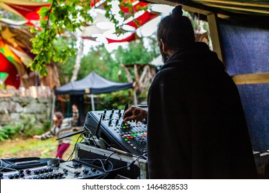 Fusion of cultural & modern music event. An over the shoulder view of a bohemian DJ using electronic music equipment to entertain people during a music festival celebrating mix of modern & old sounds