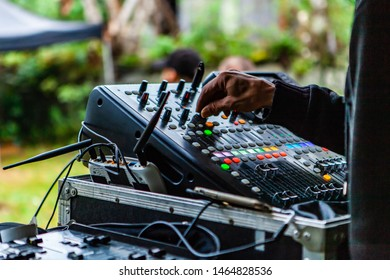 Fusion of cultural & modern music event. A close up view on the hand of a disc jockey as he operates the knobs on a modern music mixer during a live music festival outdoors.
