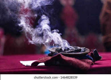 Fusion of cultural & modern music event. A close up view of embers smoking in a sacred dish during a festival of Native American cultures and traditions mystical object used by shaman, with copy space