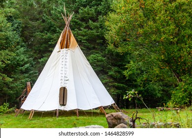 Fusion of cultural & modern music event. A rustic tipi tent is viewed by woodland, similar to that of Native American tribes, during a festival fusing ancient culture with modern music.