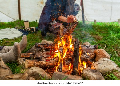 Fusion of cultural & modern music event. A closeup view of a log fire burning as people gather round to keep warm beneath a teepee tent during a traditional music festival.