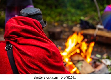 Fusion of cultural & modern music event. An over the shoulder view of a person wrapped in a red blanket sitting at a campfire outside during a traditional music gathering, with copy space to the right