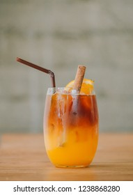Fusion drink, coffee mix with orange juice with cinnamon in glass on table next to window. Selective focus