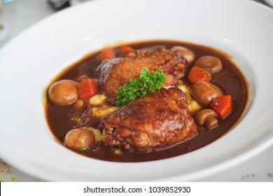 Fusion Thai style food chicken stew in red wine sauce and vegetables on white plate background restaurant recipe menu concept close up shot