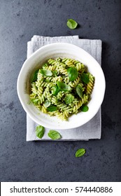 Fussili pasta with basil pesto and herbs. Italian pasta. Italian food. Home made food. Concept for a tasty and healthy meal. Gray stone background. Top view.