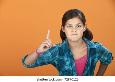 Fussy Latina child pointing index finger upward