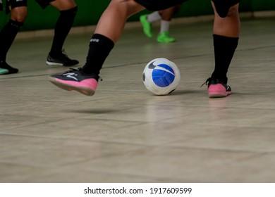 A futsal player kick a ball in indoor futsal court. Indonesia, January 21, 2021