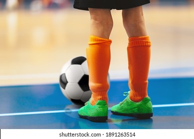 Futsal training for youth team. Young boy with soccer ball standing on white line. Indoor football soccer school practice. Kid in sportswear, black shorts, soccer cleats and orange socks