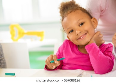 Future artist. Beautiful little African girl smiling to the camera holding coloring pen at drawing class at school education happiness childhood parenting elementary school mulatto children concept