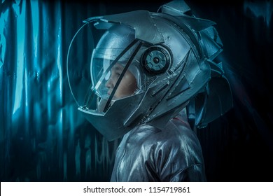 Future, Boy playing to be an astronaut with space helmet and metal suit over silver background