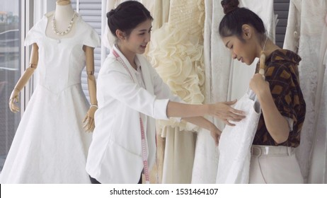 Future bride customer talking with wedding store shopkeeper to buy wedding dress and accessories for her upcoming wedding ceremony.