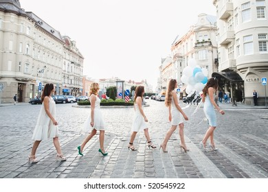The future bride with girls walking along street