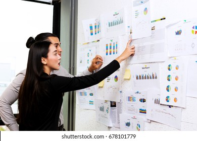 Future business leader concept. Group of young business team discussing work together in modern office. Handsome white business man and beautiful asian woman reviewing work together on white board.