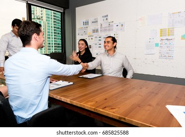 Future business leader concept. Group of young business team shaking hands in modern office. Three handsome white business men and beautiful women closing deal in meeting room.