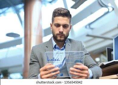 Future concept. Businessman analyzing financial statistics displayed on the futuristic transparent tablet screen.