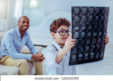 Future doctor. Positive nice boy looking at the X ray image while thinking about the diagnosis