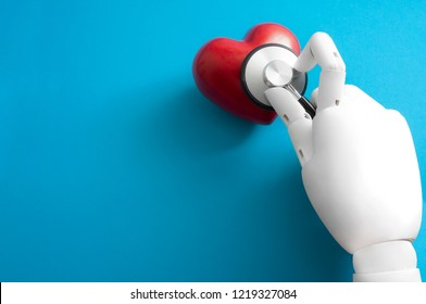 The future of healthcare and medicine, medical robotics and science fiction concept with the hand of a robot doctor using a stethoscope on a red heart isolated on a blue background with copy space